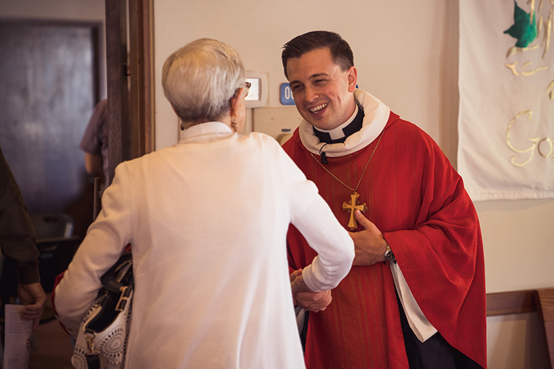 Pastor Paul Eldred greets someone before worship at Holy Cross in Bellevue